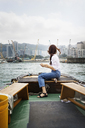 Side view of female tourist looking at buildings by sitting on boat in Hong Kong - CAVF16789