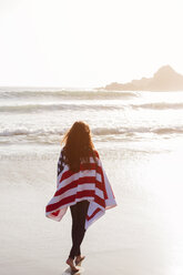 Rear view of woman wrapped in American flag walking on shore at beach - CAVF16894