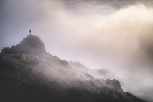 Solitude man standing on mountain during foggy weather - CAVF16918