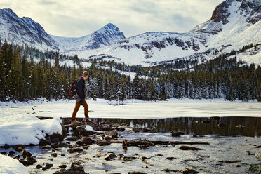 Side view of man standing on rocks at frozen lake against snowcapped mountains - CAVF16969