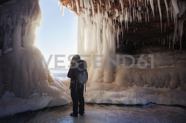 Rear view of woman standing in ice cave - CAVF16984