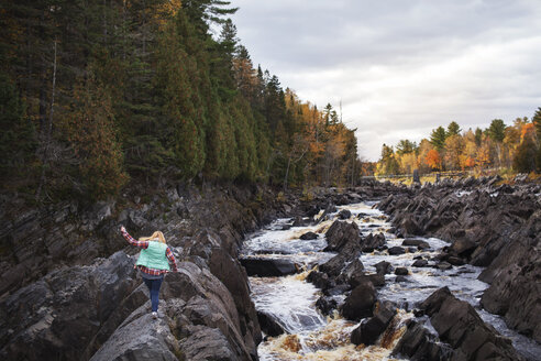 Rear view of woman walking over rocks by river at Jay Cooke State Park - CAVF17005