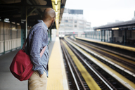 Side view of man with hand in pocket waiting for train at railroad platform - CAVF17059