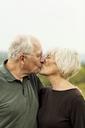 Affectionate senior couple kissing while standing against sky - CAVF17176