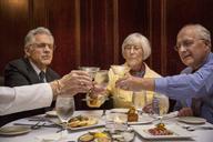 Senior friends toasting martini glasses while sitting in restaurant - CAVF17179