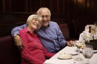 Portrait of senior couple with arm around sitting in restaurant - CAVF17185