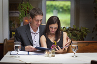 Couple reading menu while sitting in restaurant - CAVF17224