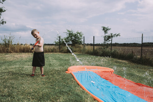 Boy playing with squirt gun by water slide at yard - CAVF17242