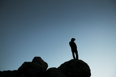 Low angle view of silhouette man standing on rock against clear blue sky at dusk - CAVF17248