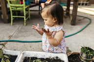 High angle view of baby girl with messy hands standing by potted plants at backyard - CAVF17281