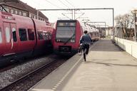 Rear view of businessman running on railroad station platform - CAVF17326