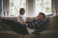 Playful family enjoying on sofa at home - CAVF17440