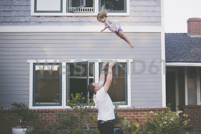 Playful father throwing daughter in air while standing in backyard - CAVF17458