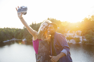 Friends taking selfie through camera by lake during sunset - CAVF17650