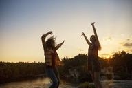 Cheerful female friends enjoying at lakeshore during sunset - CAVF17656