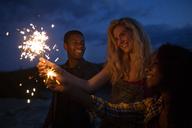 Friends holding illuminated sparklers at night - CAVF17665