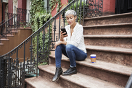 Woman using mobile phone while sitting on steps with coffee cup - CAVF17689