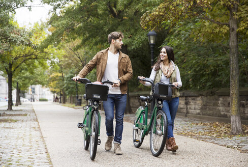 Couple talking while walking with bicycle on road at park - CAVF17752