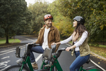 Smiling couple talking while standing with bicycles on road at park - CAVF17755