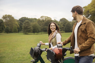 Happy couple talking while walking with bicycles in park - CAVF17758