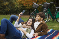 Couple taking selfie while relaxing on blanket at park - CAVF17761