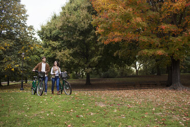 Couple talking while walking with bicycles in park - CAVF17767