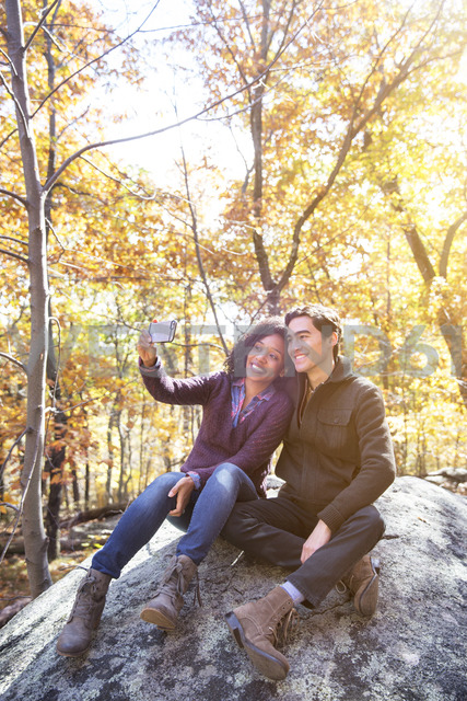 Couple taking selfie while sitting on rock in forest - CAVF17773