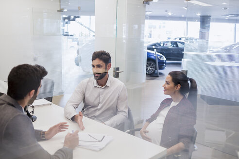 Pregnant couple talking to car salesman, discussing financial paperwork in car dealership office - CAIF19965