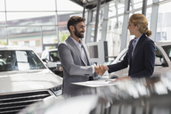 Car saleswoman and male customer handshaking in car dealership showroom - CAIF19974