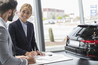Car saleswoman and male customer signing contract paperwork in car dealership showroom - CAIF19989