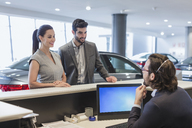 Couple customers talking to male receptionist at desk in car dealership showroom - CAIF20004
