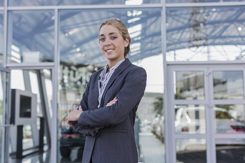 Portrait confident, smiling car saleswoman standing outside of car dealership showroom - CAIF20013