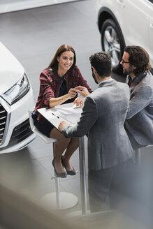 Car salesman giving car keys to smiling female customer in car dealership showroom - CAIF20016
