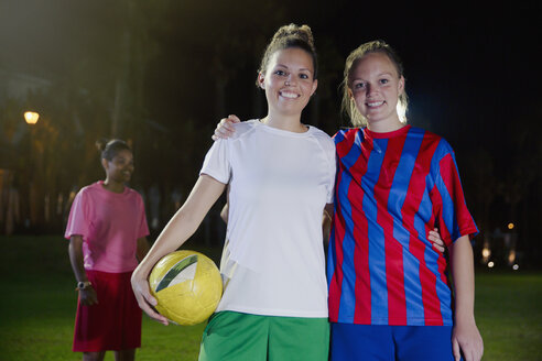 Portrait confident, smiling young female soccer teammates with ball - CAIF20109