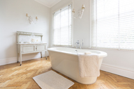 White, luxury home showcase interior bathroom with soaking tub and parquet hardwood floor - CAIF20142