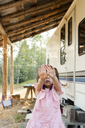 Portrait shy girl hiding face with hands outside rural camper - CAIF20205