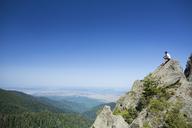 Male hiker sitting on rock against clear blue sky - CAVF17793