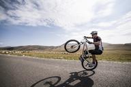 Man performing wheelie on road against sky - CAVF17835