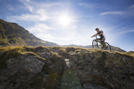 Low angle view of mountain biker riding bicycle against sky - CAVF17850
