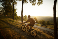 Male athlete cycling on footpath in field against clear sky - CAVF17871