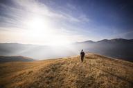 Rear view of male backpacker walking on mountain against sky - CAVF17919