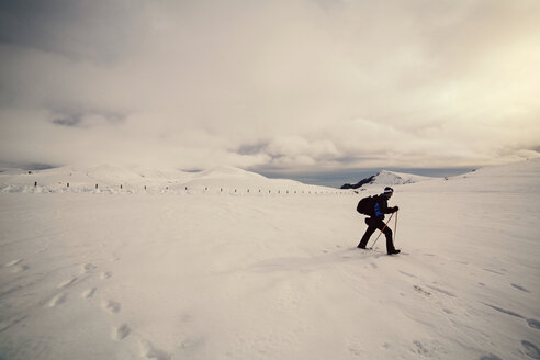 Side view of skier walking on snow against cloudy sky - CAVF17931