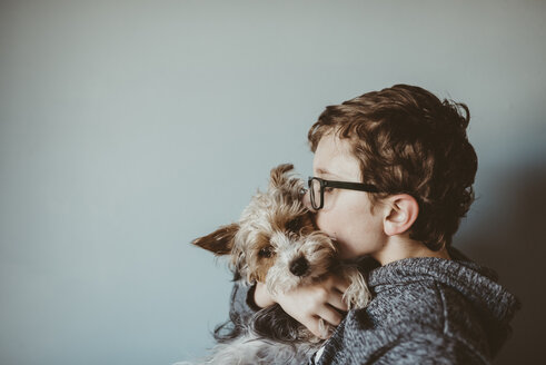 Side view of boy kissing Yorkshire Terrier against wall at home - CAVF18024