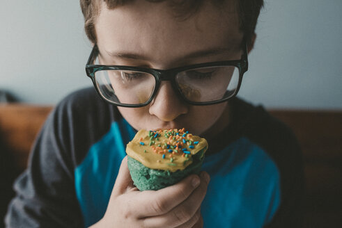 Close-up of boy eating cupcake at home - CAVF18030