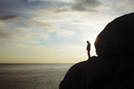 Silhouette man standing on rocky mountain by sea against sky - CAVF18060