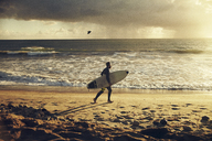 Man carrying surfboard while walking at beach during sunset - CAVF18084