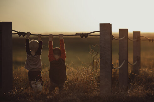 Boys hanging on fence at field during sunset - CAVF18108