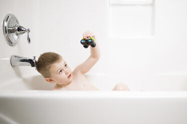 Boy playing with toy while bathing in bathtub at home - CAVF18132