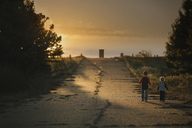 Rear view of boys walking on road against sky during sunset - CAVF18144