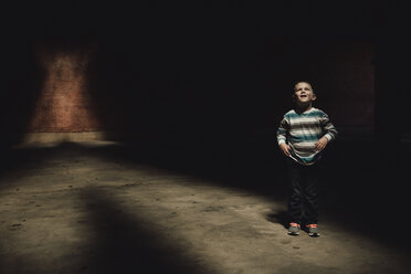 Full length of boy standing in dark room - CAVF18147